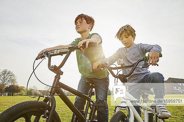 Two boys riding their BMX bikes in a park.
