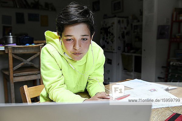 A boy sitting at a desk using a laptop for an interactive learning session  home schooling  working hard.