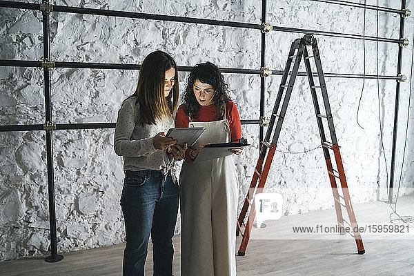 Two mid adult women looking at plans on digital tablet in their new shop