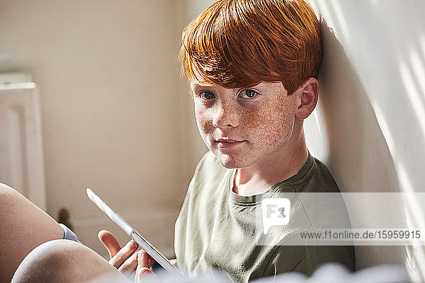 Boy with red hair sitting on floor in sunny room  holding digital tablet.