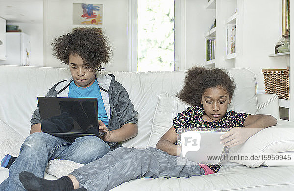 Children using laptop computers sitting on a sofa.