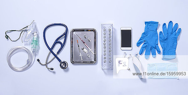 Potential way out of lockdown stage. Medical equipment on a grey background  oxygen mask  stethoscope  mobile phone with a contact tracing app  syringes for vaccine  blue gloves and digital thermometer.