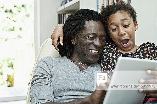 Man and daughter using a digital tablet  sharing the screen.