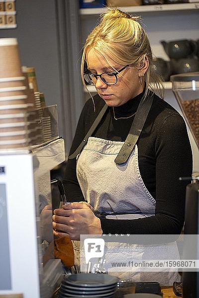 Blonde Frau mit Brille und Schürze  die an einer Espressomaschine in einem Café steht und Milch aufschäumt.