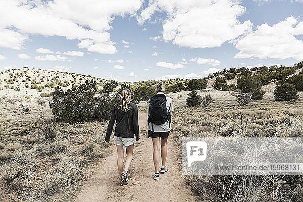Rückansicht einer erwachsenen Frau und ihrer jugendlichen Tochter beim Wandern im Galisteo-Becken  NM.