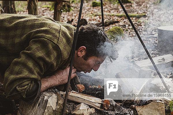 Mann legt in einem Wald ein Lagerfeuer.