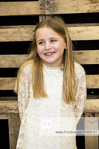 Porträt eines lächelnden Mädchens in einem cremefarbenen Spitzenkleid während der Taufzeremonie in einer historischen Scheune.