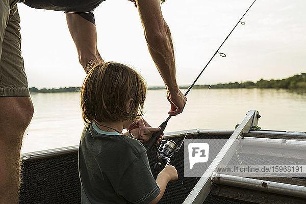 Ein fünfjähriger Junge beim Angeln von einem Boot aus auf dem Sambesi-Fluss  Botswana