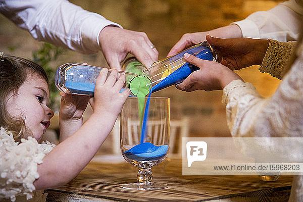 Familie gießt während der Namensgebungszeremonie in einer historischen Scheune farbigen Sand in ein Glasgefäß.