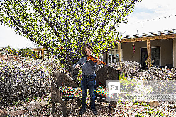 6 year old boy playing violin outside of his home