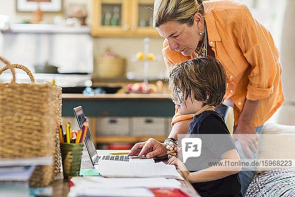 Eine erwachsene Frau hilft ihrem sechsjährigen Sohn bei einer Fernlernsitzung auf einem Laptop mit einem Touchpad.