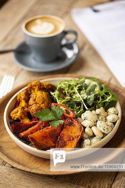Nahaufnahme einer Schüssel mit gemischtem Gemüse in einem Cafe aus einem hohen Winkel.