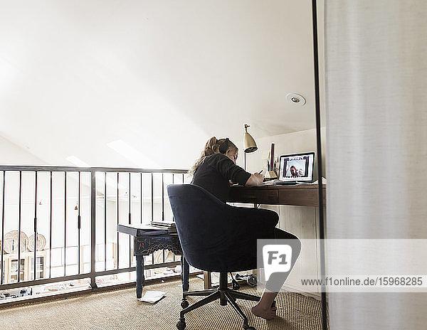14-jähriges Mädchen betrachtet Laptop auf ihrem Dachboden