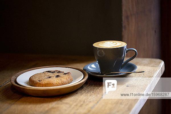 Nahaufnahme einer Tasse Cappuccino und eines Schokokekses auf einem Teller in einem Café.