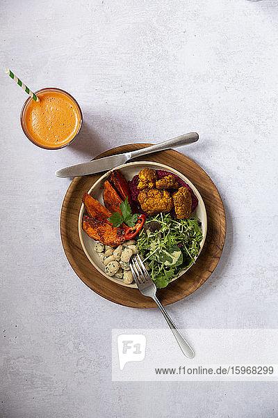 Nahaufnahme eines Glases mit Karottensaft und einer Schüssel mit gemischtem Gemüse in einem Cafe.