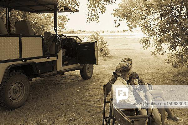 Drei Generationen einer Familie sitzen in Klappstühlen in einem Safarijeep  unter Bäumen  einfarbig.