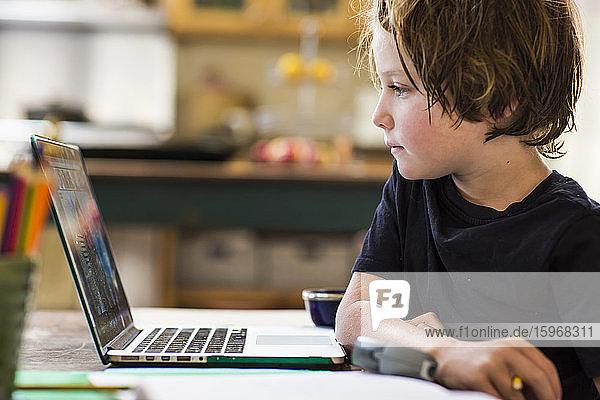 6-jähriger Junge  der eine Fernschulung mit seinem Lehrer hat