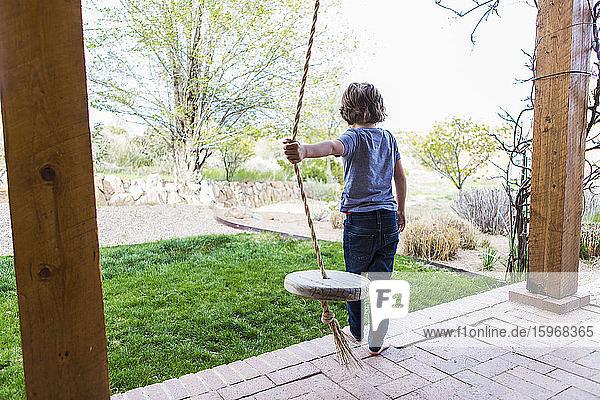 Sechsjähriger Junge  der mit einer Seilschaukel auf einer breiten Veranda im Schatten schaukelt.