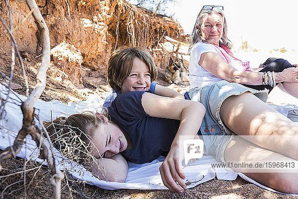 Zwei Kinder und Großmutter im Hintergrund  die sich nach einer Wanderung ausruhen