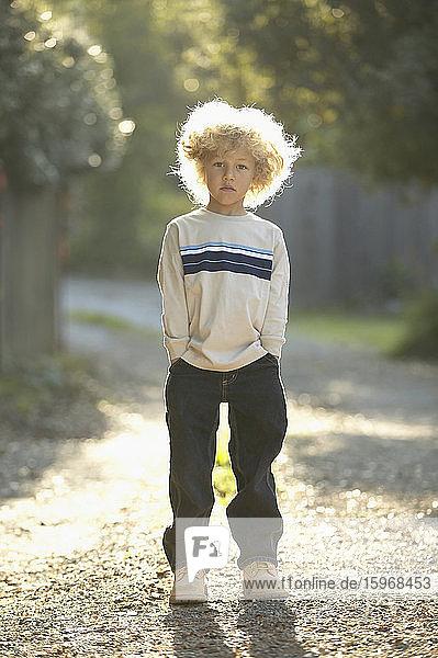 Junge steht auf einem Kiesweg  Hände in den Taschen.