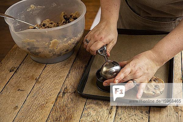 Nahaufnahme einer Person  die an einem Holztisch steht und Schokoladenkekse backt.