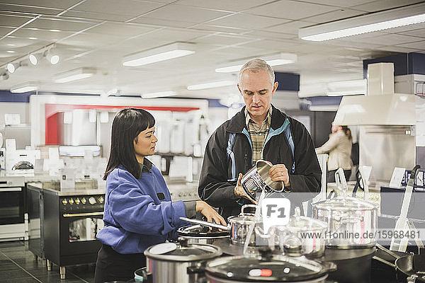Junger Besitzer zeigt Küchengerät vor reifem Kunden im Geschäft