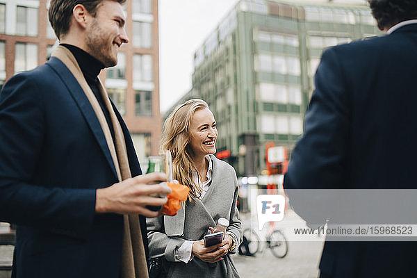 Lächelnde Unternehmerin mit männlichen Kollegen in der Stadt