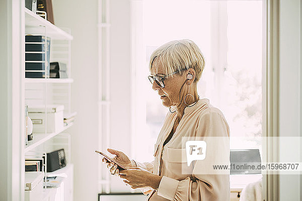 Woman in home office using smartphone