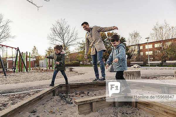 Playful father with children in playground during sunset