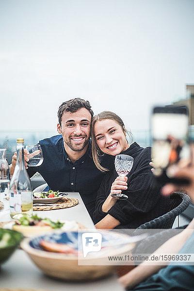 Glückliche Freunde mit Getränken  die während der Dachparty zum Fotografieren posieren