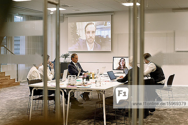 Business executives discussing in meeting during web conference seen through glass at office