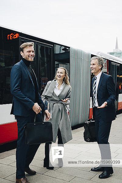 Lächelnde Geschäftsfrau mit männlichen Kollegen steht in der Stadt gegen Bus