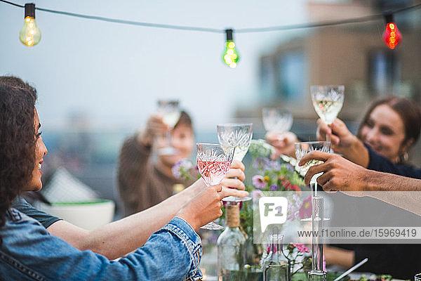 Junge Freunde stoßen während des geselligen Beisammenseins auf der Gebäudeterrasse auf Getränke an Junge Freunde stoßen während des geselligen Beisammenseins auf der Gebäudeterrasse auf Getränke an