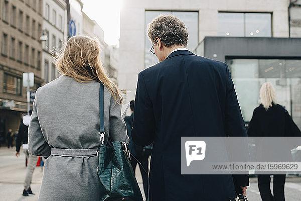 Rückansicht eines weiblichen Geschäftsmannes mit männlichem Mitarbeiter in der Stadt