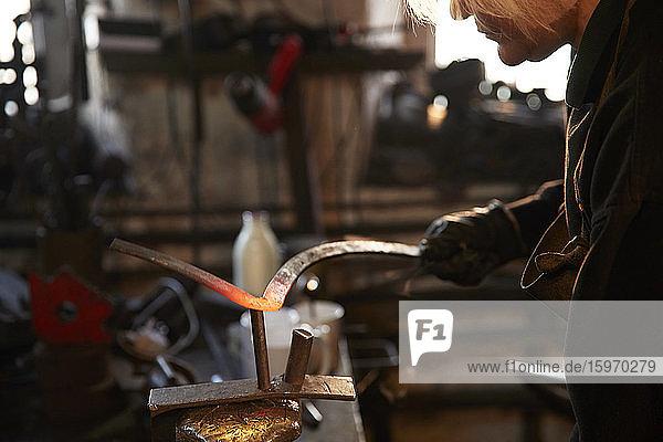 Schmiedin formt Stahl in der Werkstatt