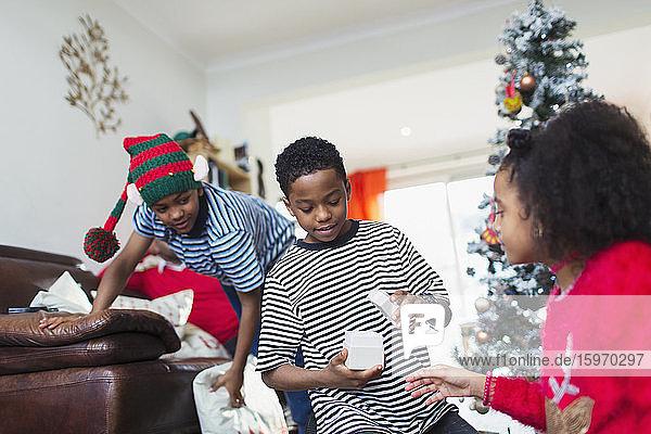 Familie öffnet Weihnachtsgeschenk im Wohnzimmer