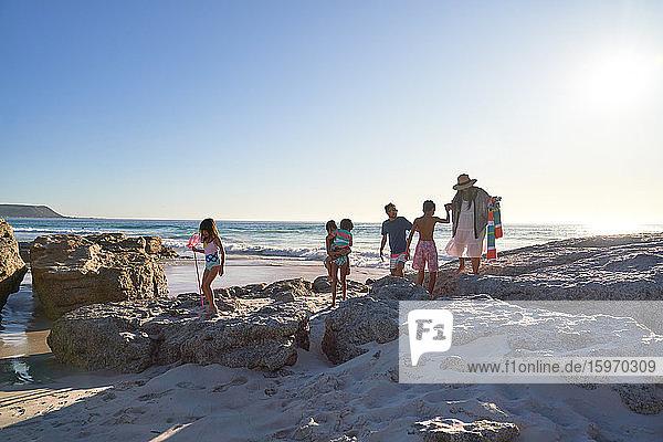 Familie spielt auf Felsen am sonnigen Strand des Ozeans  Kapstadt  Südafrika