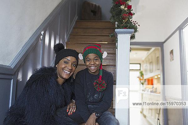 Porträt einer glücklichen Mutter und ihres Sohnes mit Weihnachtshüten auf der Treppe