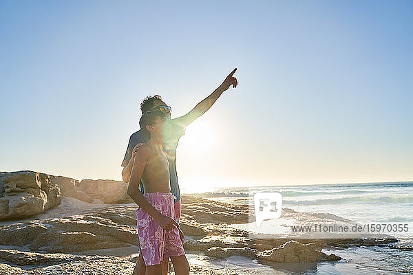 Vater und Sohn zeigen am sonnigen Strand des Ozeans in den Himmel