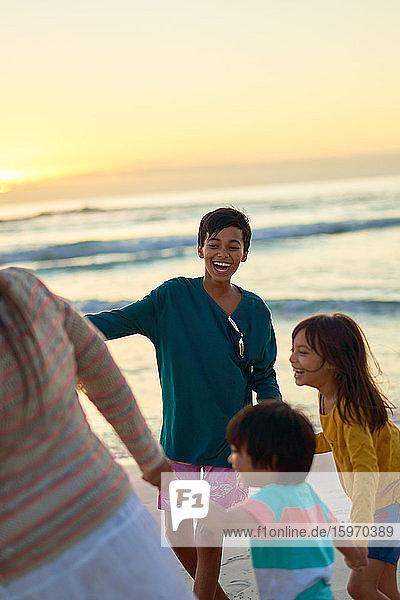Glückliche Familie spielt am Strand bei Sonnenuntergang