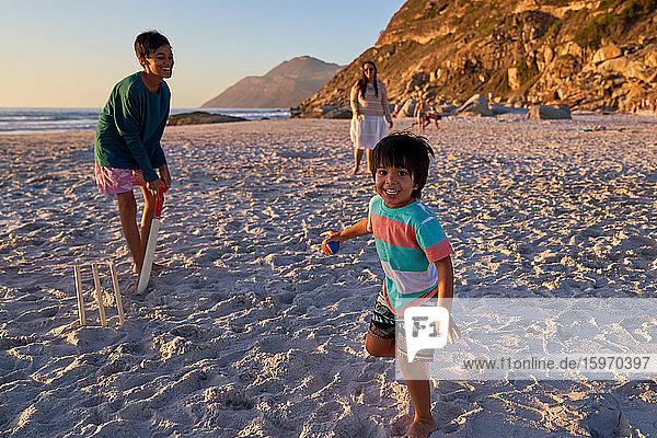 Porträt einer glücklichen Familie beim Kricketspielen am sonnigen Strand