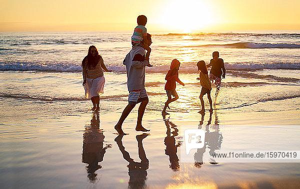 Familie watet bei Sonnenuntergang am idyllischen Meeresstrand in der Brandung
