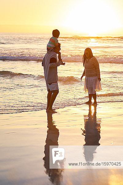 Familie watet bei Sonnenuntergang in der Brandung