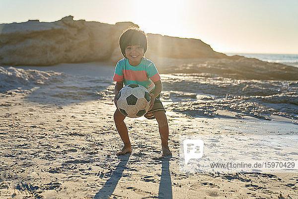 Porträt eines süßen Jungen  der mit einem Fussball am sonnigen Strand spielt