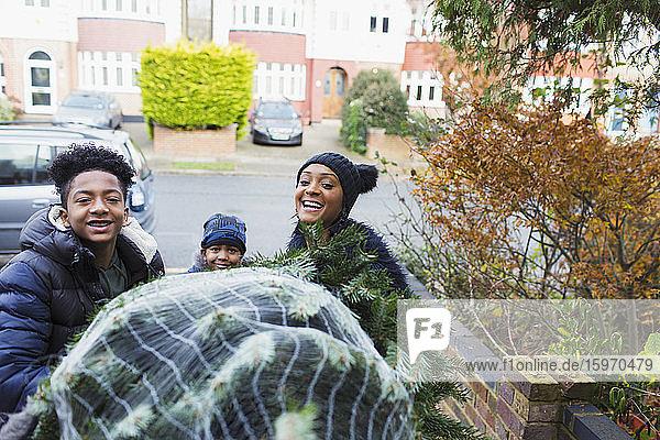 Porträt glückliche Familie mit Weihnachtsbaum in der Einfahrt