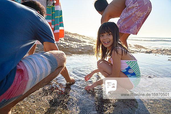 Porträt eines glücklichen Mädchens  das mit seiner Familie am sonnigen Strand im Gezeitenbecken spielt