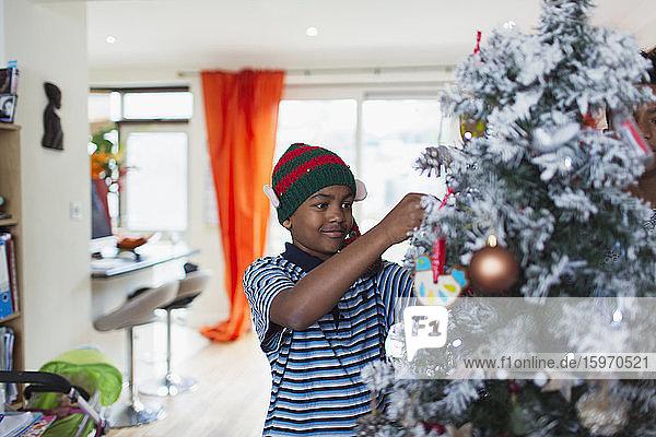 Junge schmückt Weihnachtsbaum im Wohnzimmer