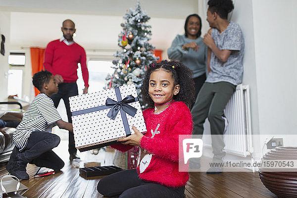 Porträt eines glücklichen Mädchens mit Weihnachtsgeschenk im Wohnzimmer