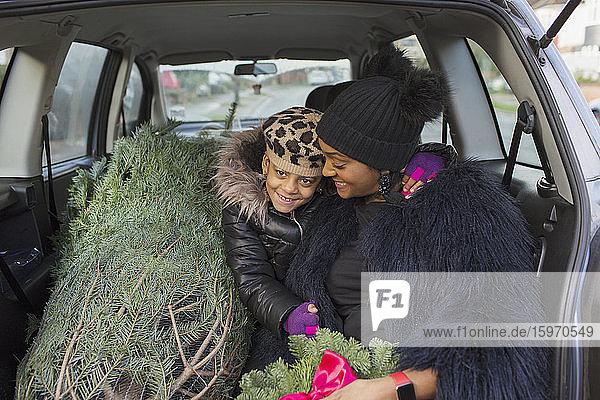 Porträt glückliche Mutter und Tochter im Auto mit Weihnachtsbaum