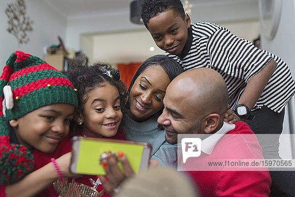 Glückliche Familie nimmt Weihnachts-Selfie mit Smartphone
